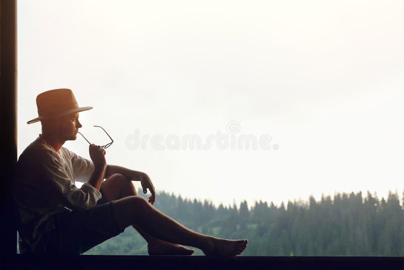 Equipaggi il rilassamento di seduta ed il pensiero con i vetri a disposizione sul portico immagini stock
