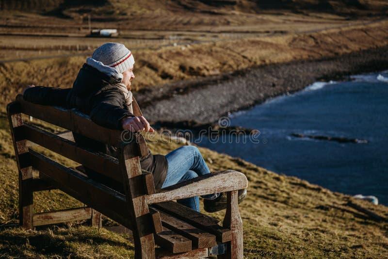 Equipaggi il rilassamento su un banco di legno dall'acqua sull'isola del cielo, Scozia immagini stock