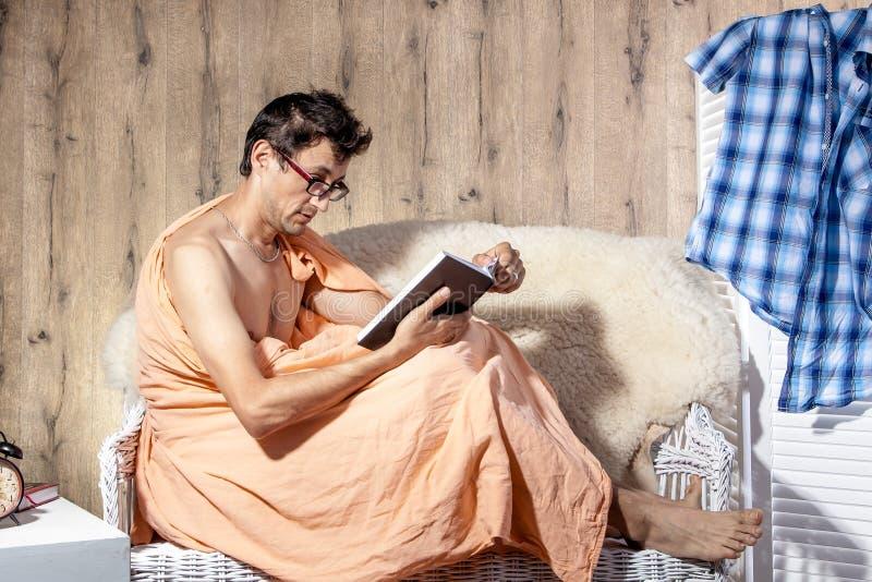 Equipaggi il rilassamento sul libro novello di storia della lettura dello strato del sofà fotografie stock