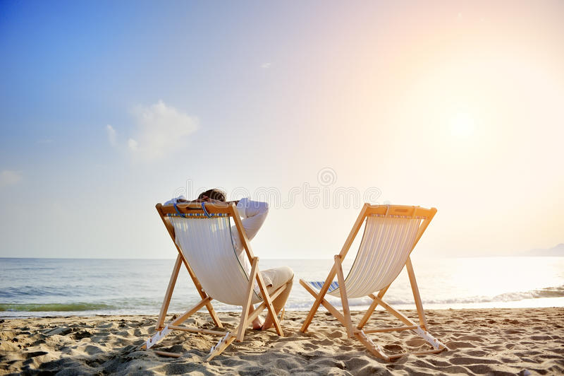 Equipaggi il rilassamento sulla spiaggia che si siede sullo sdraio immagine stock libera da diritti