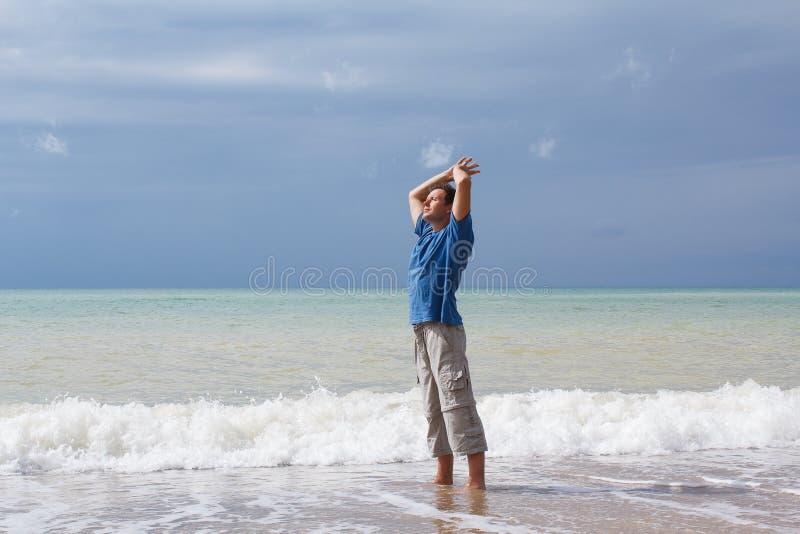 Equipaggi il rilassamento sulla spiaggia e sull'onda imminente fotografia stock