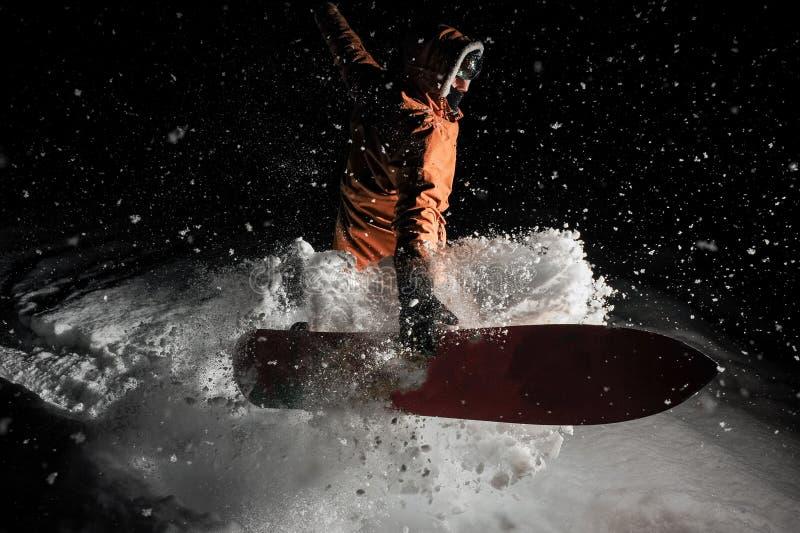 Equipaggi il salto con lo snowboard nella località di soggiorno di montagna nel nig immagini stock