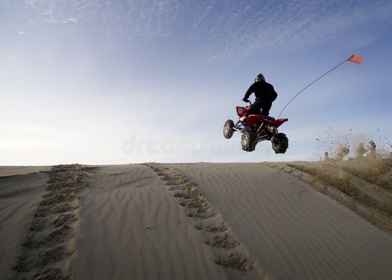 Equipaggi il salto del suo quadrato sopra una duna di sabbia immagine stock libera da diritti