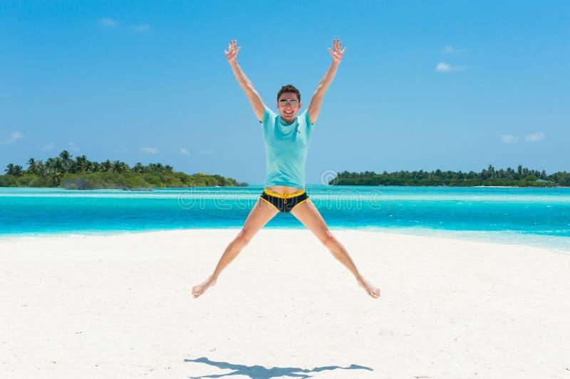 Equipaggi il salto sulla spiaggia con due isole sui precedenti, felicità immagine stock libera da diritti