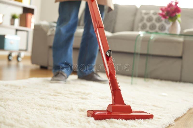 Equipaggi il tappeto di pulizia con un aspirapolvere nella sala immagine stock