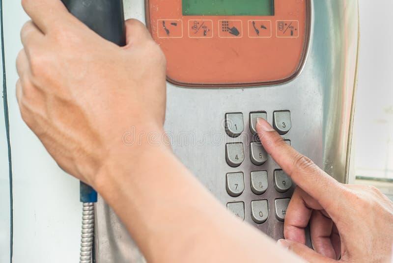 Equipaggi il telefono pubblico di uso che preme il numpad il numero 2 immagini stock libere da diritti