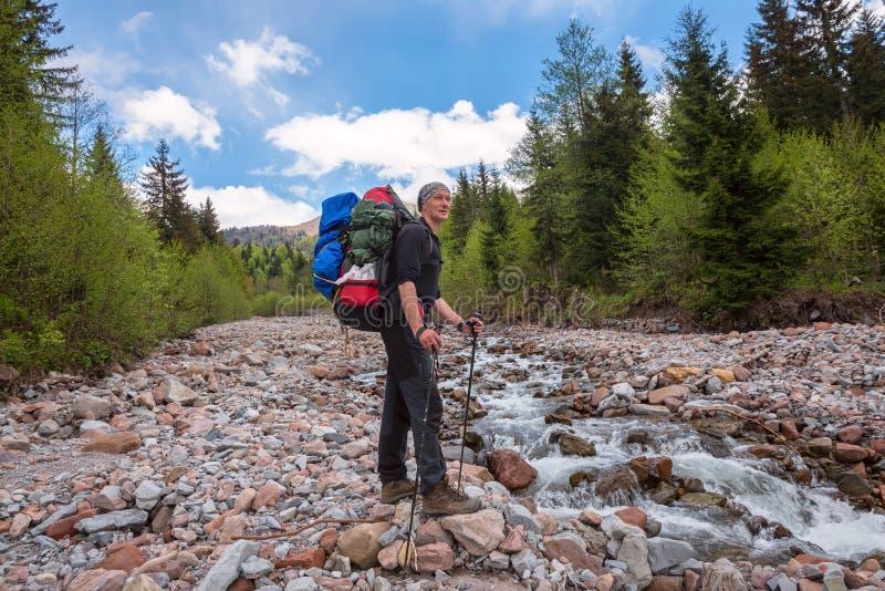 Equipaggi il viaggiatore con gli incroci dello zaino un fiume della montagna immagini stock