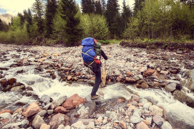 Equipaggi il viaggiatore con gli incroci dello zaino un fiume della montagna Ima d'annata immagini stock