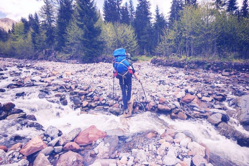 Equipaggi il viaggiatore con i grandi incroci dello zaino un fiume della montagna fotografie stock libere da diritti