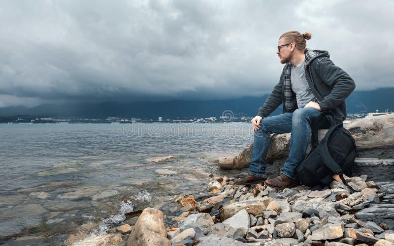 Equipaggi il viaggiatore con i seets di uno zaino sulla spiaggia contro un fondo delle nuvole e un concetto della catena montuosa immagine stock