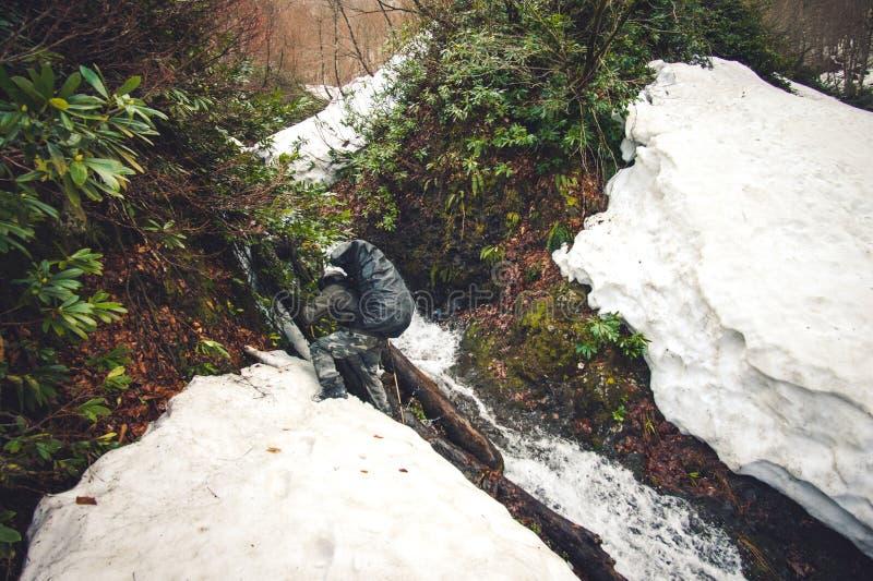 Equipaggi il viaggiatore con la cascata dell'incrocio dello zaino ed il ghiacciaio della neve fotografia stock libera da diritti