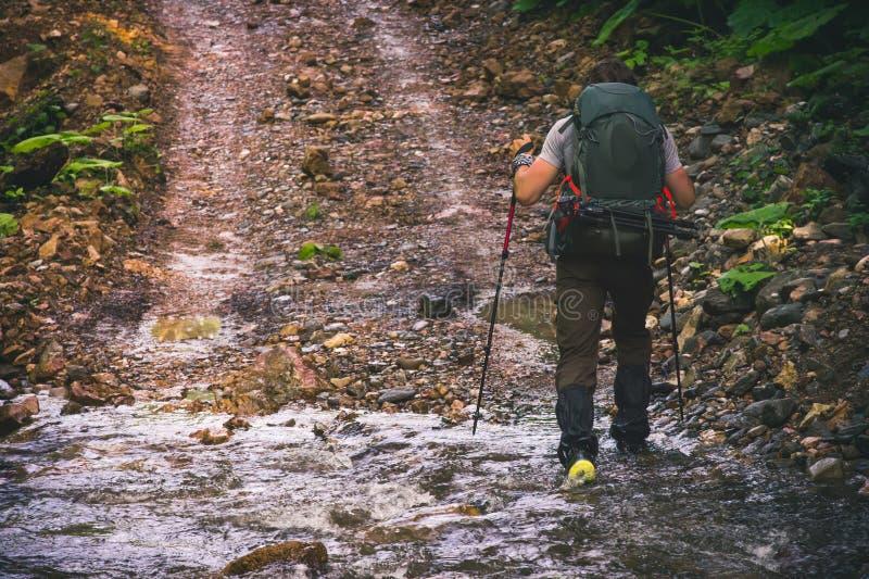 Equipaggi il viaggiatore con lo zaino che fa un'escursione lo stile di vita all'aperto di viaggio fotografia stock