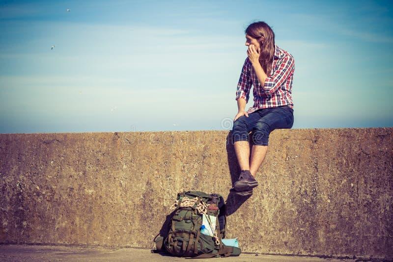 Equipaggi il viaggiatore con zaino e sacco a pelo turistico che si siede sulla parete di lerciume all'aperto fotografia stock libera da diritti