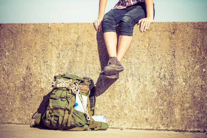 Equipaggi il viaggiatore con zaino e sacco a pelo turistico che si siede sulla parete di lerciume all'aperto immagine stock