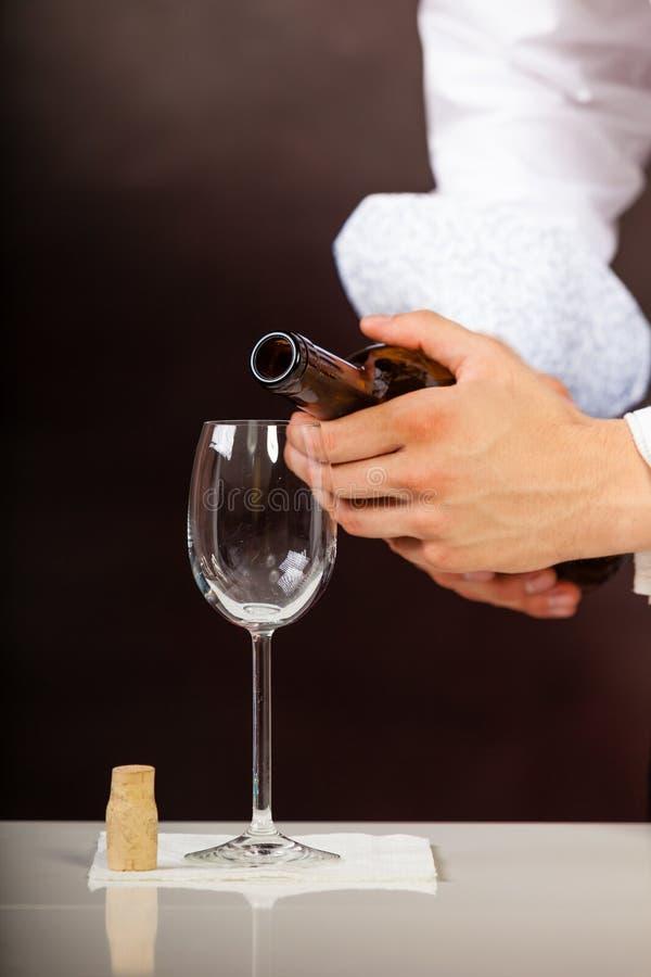 Equipaggi il vino bianco di versamento del cameriere in vetro immagini stock libere da diritti