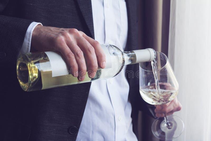 Equipaggi il vino bianco di versamento in un vetro fotografia stock libera da diritti