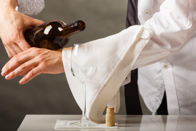 Equipaggi il vino di versamento del cameriere in vetro fotografia stock
