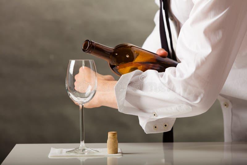 Equipaggi il vino di versamento del cameriere in vetro immagine stock