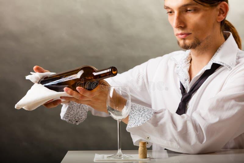 Equipaggi il vino di versamento del cameriere in vetro immagini stock