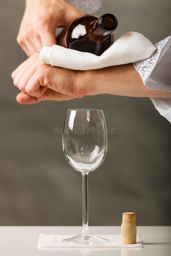 Equipaggi il vino di versamento del cameriere in vetro immagini stock libere da diritti