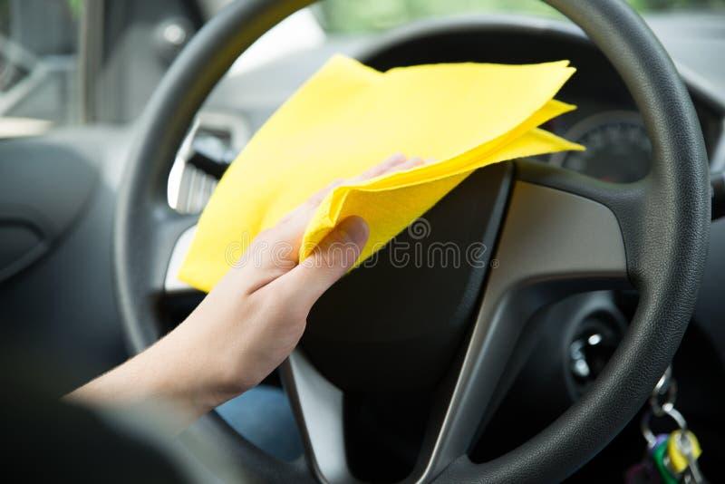 Equipaggi il volante di pulizia dell'automobile con il panno fotografia stock