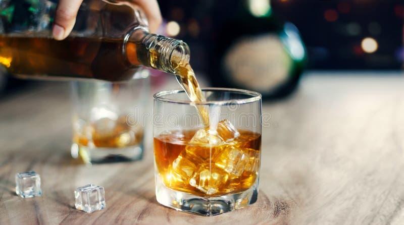 Equipaggi il whiskey di versamento nei vetri, beventi la bevanda alcolica immagini stock libere da diritti
