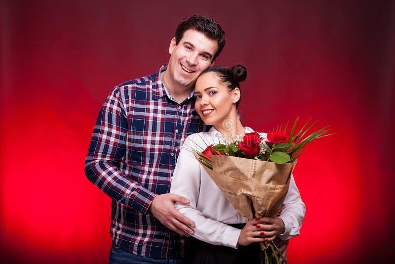 Equipaggi l'abbraccio della sua moglie bella mentre tiene un mazzo delle rose fotografie stock libere da diritti