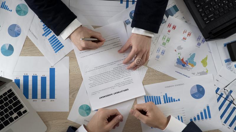 Equipaggi l'accordo di occupazione di firma, responsabile di ora che impiega il nuovo impiegato, vista superiore fotografia stock libera da diritti
