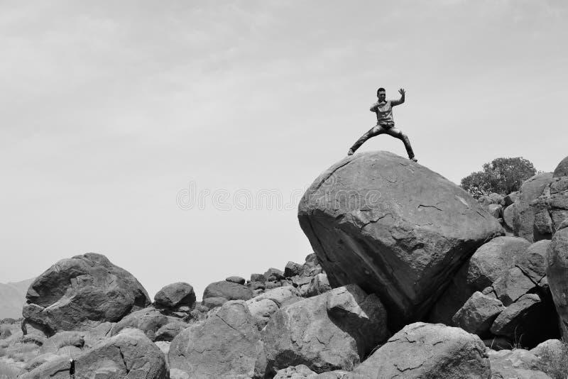 Equipaggi l'addestramento sulle arti marziali su un mucchio delle rocce nel deserto #3 immagini stock