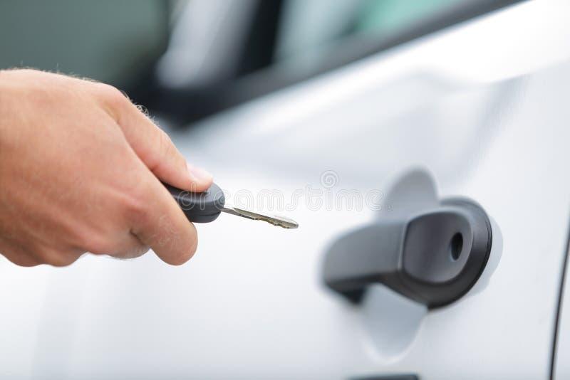 Equipaggi l'autista che sblocca o che chiude la porta a chiave di automobile con la chiave immagini stock