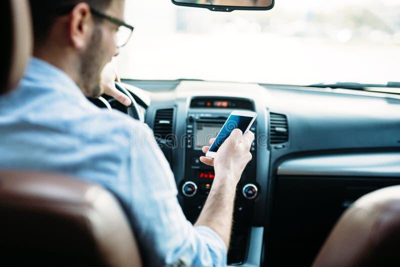 Equipaggi l'autista che utilizza lo Smart Phone sulla strada nell'automobile fotografia stock libera da diritti