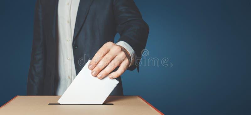 Equipaggi l'elettore che mette il voto nella scatola di voto Concetto di libertà di democrazia su fondo blu fotografie stock