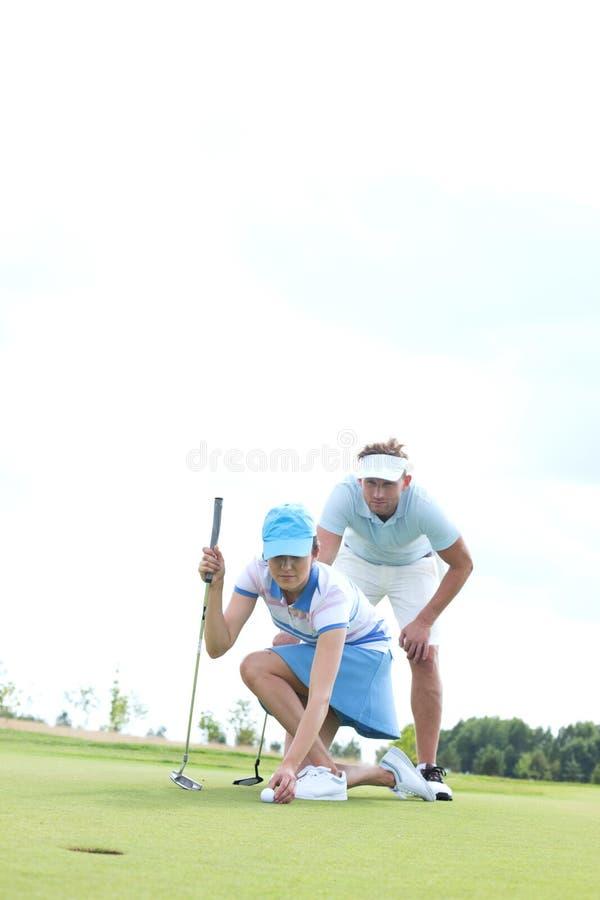 Equipaggi l'esame della donna che tende la palla sul campo da golf contro il cielo immagine stock libera da diritti