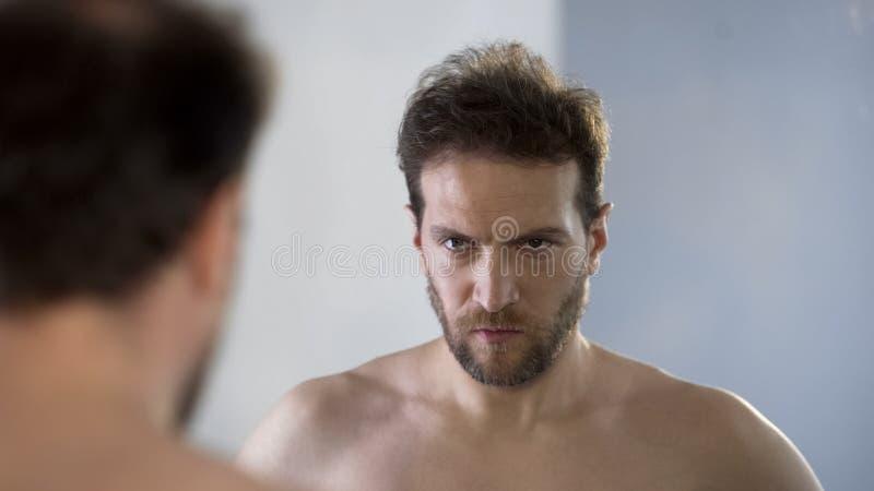 Equipaggi l'esame della sua riflessione di specchio con odio e vergogna, ritenenti colpevoli fotografia stock
