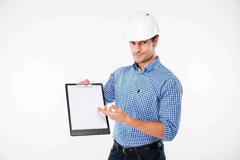 Equipaggi l'ingegnere di costruzione in casco che indica sulla lavagna per appunti in bianco immagine stock libera da diritti