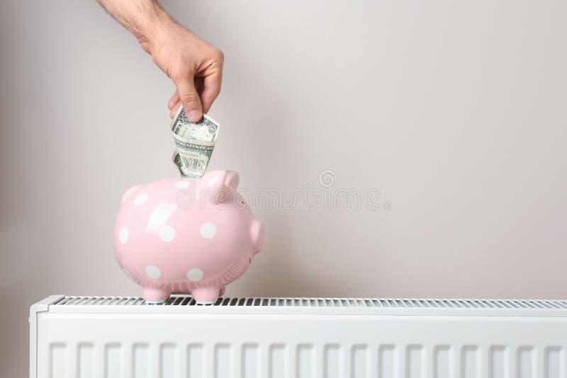 Equipaggi l'inserimento dei soldi nel porcellino salvadanaio fotografia stock