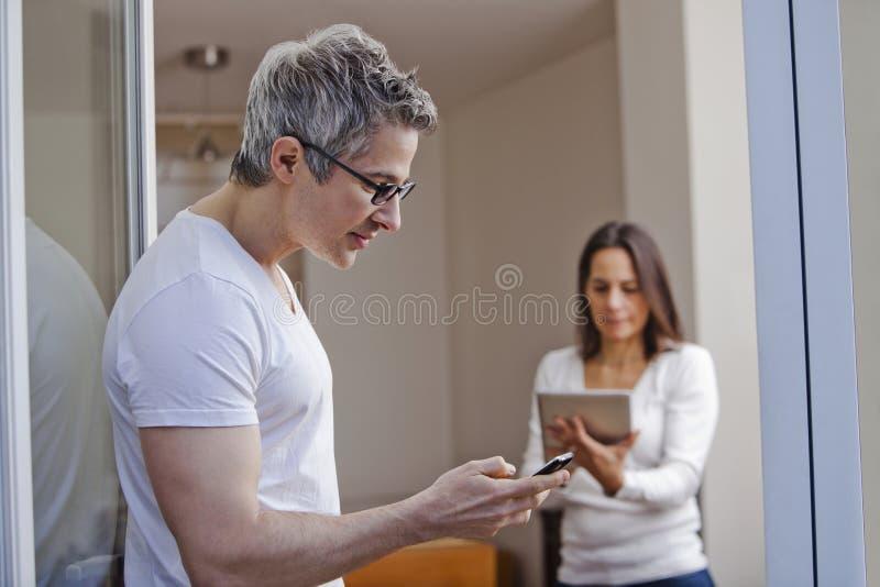 Equipaggi l'invio di messaggi di testo con la sua moglie che per mezzo di una compressa digitale immagini stock libere da diritti