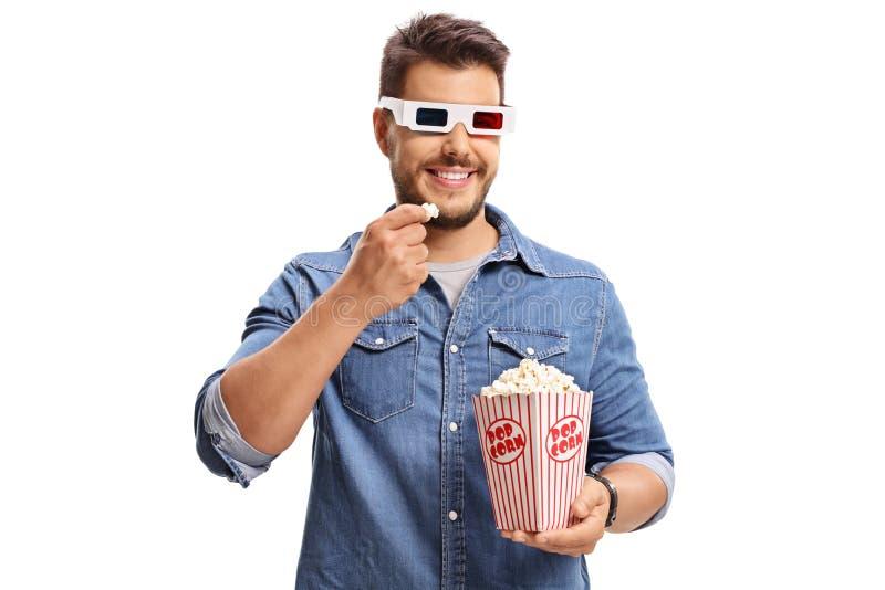 Equipaggi l'uso del paio dei vetri 3D ed il cibo del popcorn fotografia stock