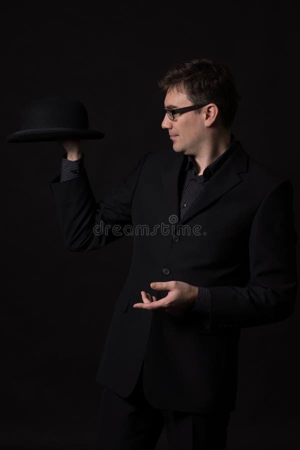 Equipaggi l'uso del vestito nero che tiene un cappello di giocatore di bocce in una mano immagini stock libere da diritti