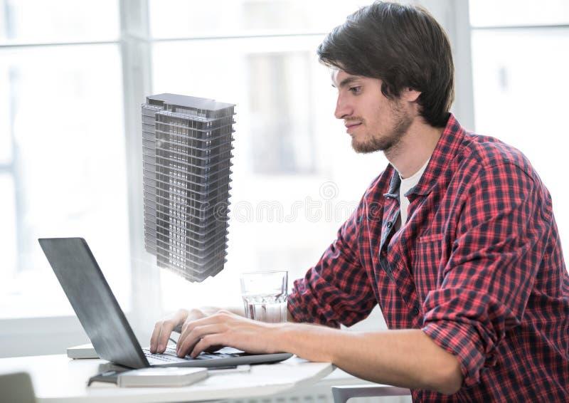 Equipaggi la battitura a macchina sul computer portatile con il modello della costruzione dell'architettura 3D fotografia stock libera da diritti