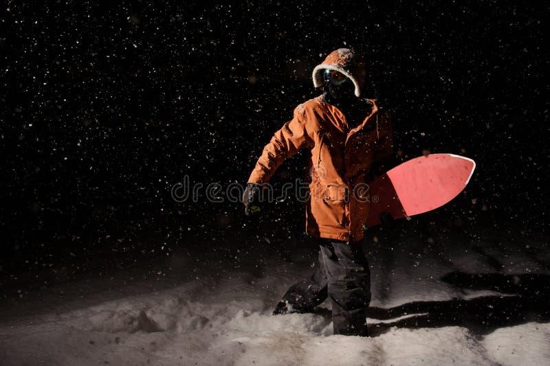 Equipaggi la camminata con lo snowboard nella località di soggiorno di montagna nel nig immagini stock libere da diritti