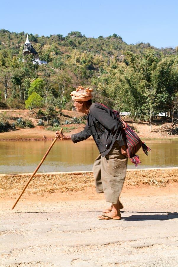 Equipaggi la camminata con un bastone nella campagna di Pindaya su Myanma immagini stock