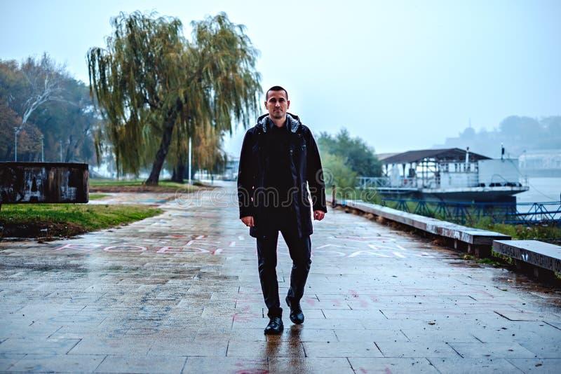 Equipaggi la camminata dal fiume un giorno piovoso fotografia stock