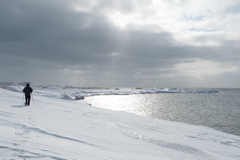 Equipaggi la camminata in racchette da neve su neve alla spiaggia fotografia stock