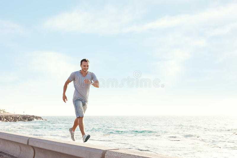 Equipaggi la camminata sopra il pilastro vicino all'oceano con le cuffie e la musica immagine stock libera da diritti