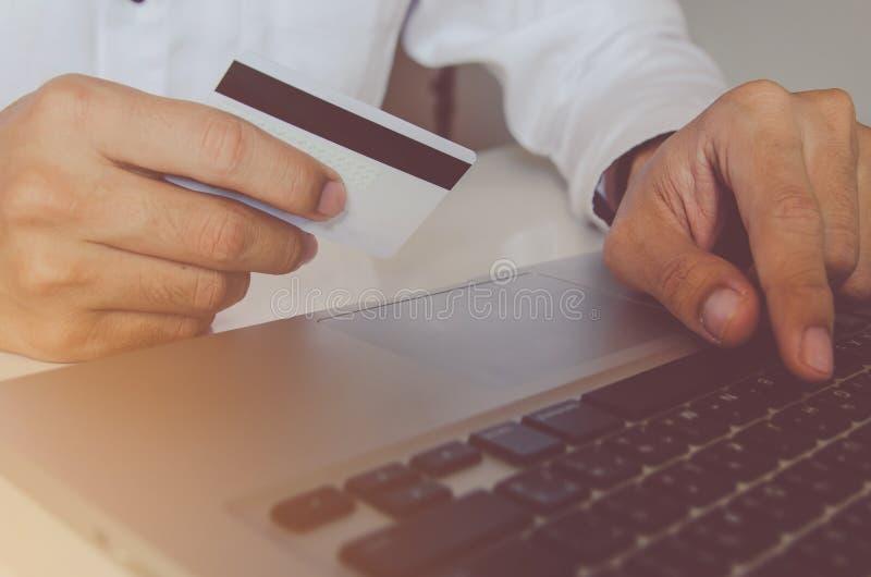Equipaggi la carta di credito della tenuta della mano e computer portatile usando che fa il paym online immagine stock libera da diritti