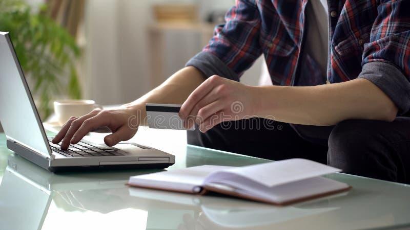 Equipaggi la carta di credito della tenuta, scrivendo sul computer portatile, pagando le utilità, comperante online immagine stock libera da diritti