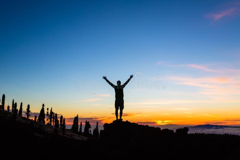 Equipaggi la celebrazione del tramonto con le armi stese in montagne immagine stock libera da diritti