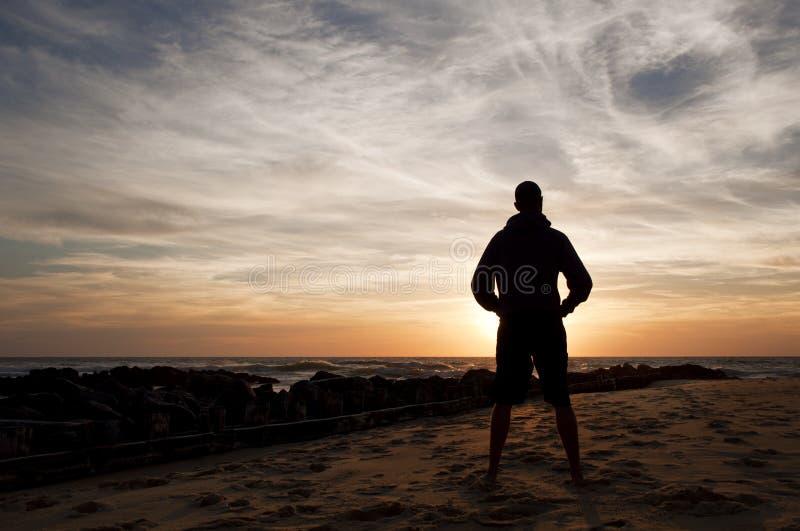 Equipaggi la condizione che esamina il tramonto nella spiaggia fotografia stock libera da diritti
