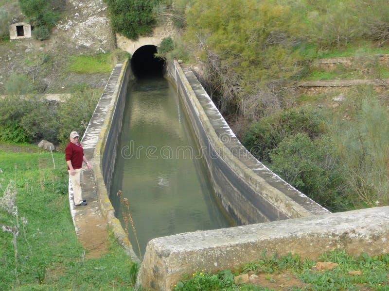 Equipaggi la condizione sul bordo del canale concreto di irregation del aquaduct fotografia stock
